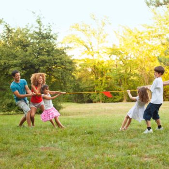 Two Families having fun playing tug of wars outdoors, after barbecue party. One Caucasian family and other mixed race family.